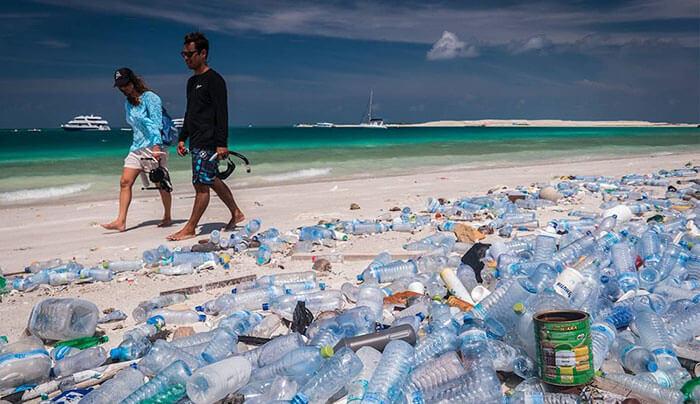 hình ảnh cặp đôi đi trên biển với đầy chai nhựa được vứt lung tung